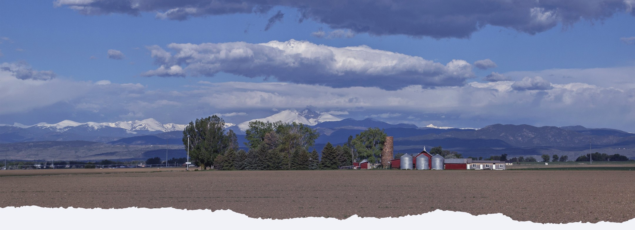 Red Barn with Silos and Large Trees with the Colorado Front Range Mountains Behind the Farm
